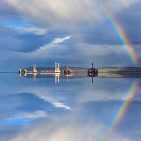 oilrig: Semi Submersible Oil Rigs and Rainbow with Reflection at Cromarty Firth in Invergordon, Scotland Stock Photo
