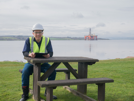front desk: An asian engineer sitting on the desk in front of semi submersible oil rig