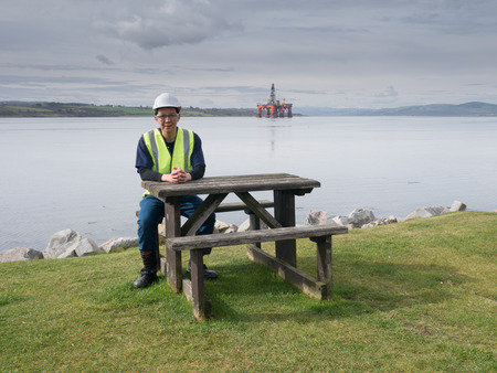 oilrig: An asian engineer sitting on the desk in front of semi submersible oil rig