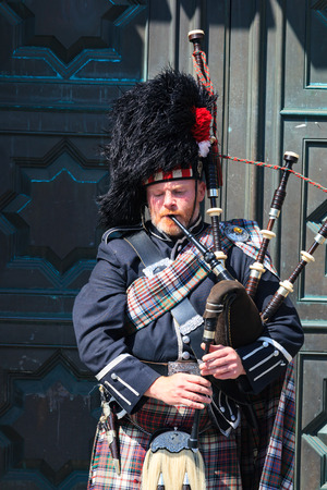 bagpipes: EDINBURGH, SCOTLAND - MAY 29, 2016: A Scotsman wearing traditional Scottish outfit playing the bagpipes along the Royal Mile in Edinburgh, on 29th March 2016.
