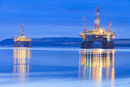 クロマーティ インヴァーゴードン、スコットランドのファースの日の出中に半潜水艇石油リグ