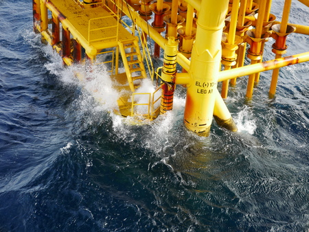oilwell: High wave hitting the Boat Landing and Producing Slots at Offshore Platform during bad weather conditions (high wave) - Oil and Gas Industry Stock Photo