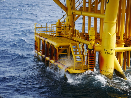 High wave hitting the Boat Landing and Producing Slots at Offshore Platform during bad weather conditions (high wave) - Oil and Gas Industry Stock Photo