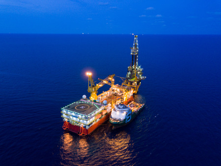Aerial View of Tender Drilling Oil Rig (Barge Oil Rig) in The Middle of The Ocean at Surise Time 写真素材