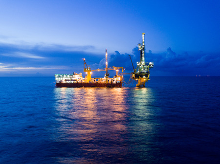 sun energy: Aerial View of Tender Drilling Oil Rig (Barge Oil Rig) in The Middle of The Ocean at Sunrise Time Stock Photo