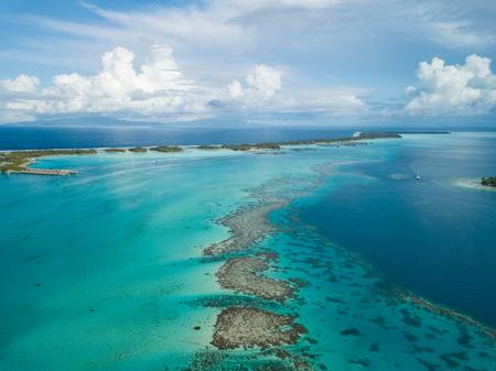 Luxury overwater villas with coconut palm trees, blue lagoon, white sandy beach at Bora Bora island, Tahiti, French Polynesia Stockfoto