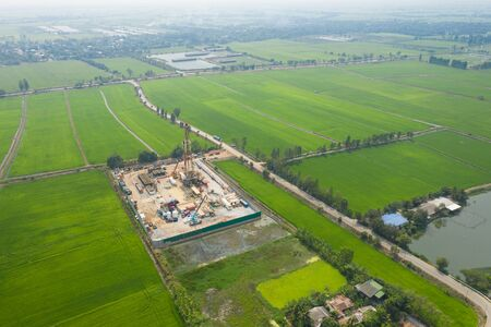 Oil and gas land drilling rig onshore in the middle of a rice field aerial view from a drone
