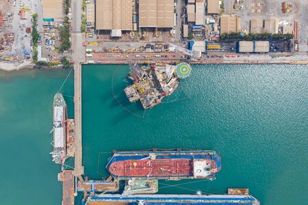 Aerial view of a jack up oil drilling rig and dry dock ship in the shipyard for maintenance