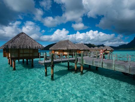 BORA BORA, FRENCH POLYNESIA - SEPTEMBER 5, 2018 - Luxury overwater villas on blue lagoon, white sandy beach and Otemanu mountain at Bora Bora island, Tahiti, French Polynesia