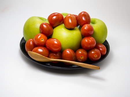 black dish: cherry Tomato and Green Apple on black dish on White background Stock Photo