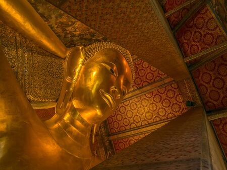 recline: Bangkok, Thailand - January 22, 2016. Reclining Buddha gold statue face. Many tourist coming to visit Wat Pho the beautiful temple