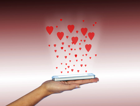 media love: Mobile phone in woman hand. With many red hearts.