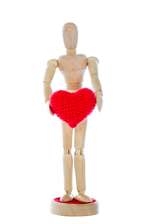 love confession: Love confession with wooden dummy holding a red heart yarn in its hands. Valentines Day on white background