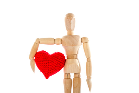 confession: Love confession with wooden dummy holding a red heart yarn in its hands. Valentines Day on white background