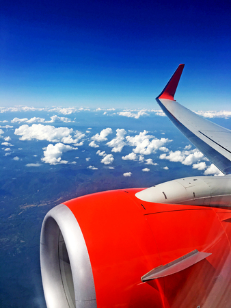 looking through window: Looking through window aircraft during flight in wing with a blue sky Stock Photo
