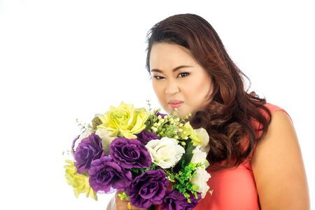 pinches: Young woman pinches her nose with flowers stink Stock Photo