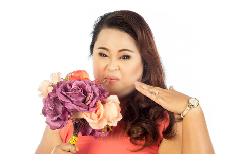 fully unbuttoned: Young woman pinches her nose with flowers stink Stock Photo