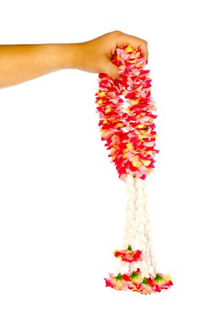 extending: Asian womans hand holding garland isolated on white background