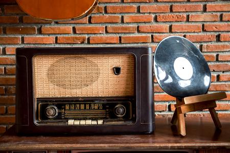 Obsolete radio on wooden, brick wall background
