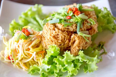 Crispy Catfish Salad Served white plate, Shredded Green Mango, Red Onion, Cabbage, Chili, Peanut