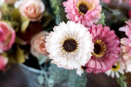 Artificial flower in the pot over wood table Imagens