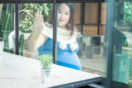 Pregnant woman is in a room with mirrors Stock fotó