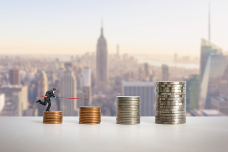 Mini dolls and Stacks of coins in a growth financial concept.