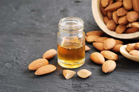 Almonds oil in a clear glass bottles and pile of roasted almonds on black wooden plank, copy space concept. Banque d'images