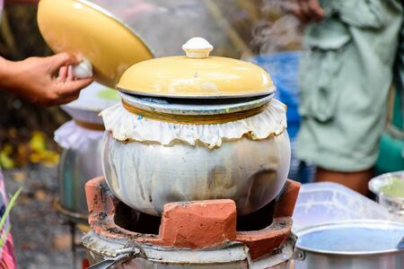 lid: cooking pot with yellow lid on fireplace Stock Photo