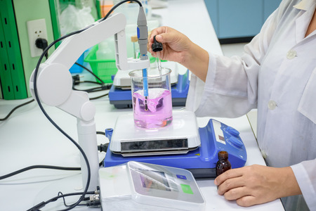 Scientist dropping fluid to sample in beaker placed on magnetic stirrer