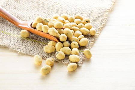 Aroma ricoperto di alghe di arachidi con cucchiaio di legno sul sacco di canapa, tavolo di legno