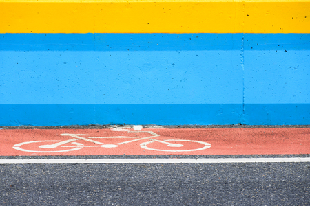 Bicycle lane with sign on red painted with blue and yellow barrier Stock Photo
