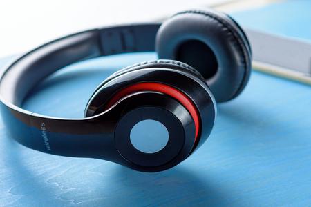 Wireless headphone on blue wooden table