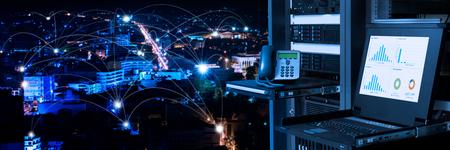 Management- und Überwachungsmonitor in Rechenzentrum und Verbindungslinien über Nachtstadthintergrund, intelligentes Stadtkonzept