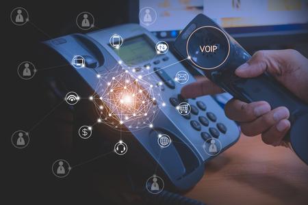 Mano del hombre que usa el teléfono ip con el icono volador de los servicios de voip y el concepto de conexión de personas, voip y telecomunicaciones