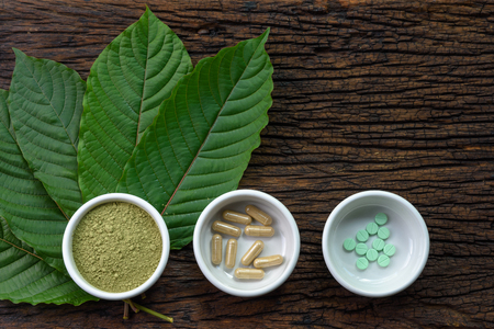 Mitragyna speciosa (kratom) leaves with medicine products in powder, capsules and tablet in white ceramic bowl with wooden texture on background 写真素材