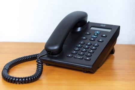 Black ip telephone device on wooden table Banco de Imagens