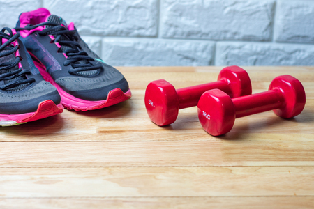 Dumbbells and sport shoes on wooden floor, fitness concept
