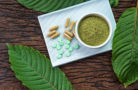Mitragyna speciosa or kratom leaves with medicinal products in pills, capsules and powder in white ceramic bowl and wooden table, top view