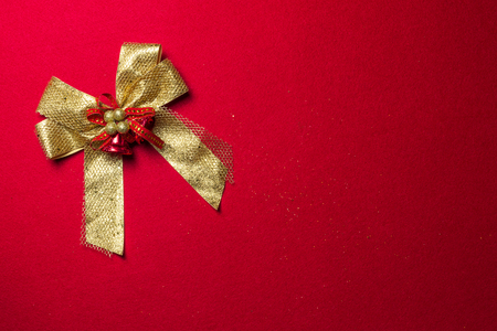 Golden ribbon bow with decorations on red flannel background, top view design Standard-Bild - 121164011