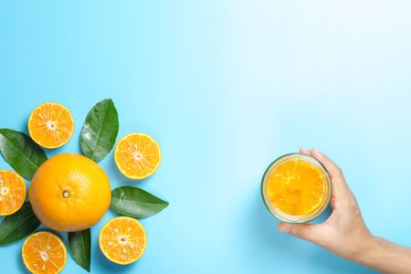 Hand of woman holding glass of orange juice and orange fruits with sliced pieces and leaves on blue background, flat design Banque d'images - 130898779