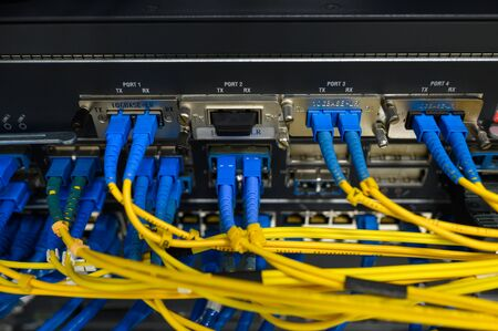 Network core switch front panel with fiber optics patch cord connected Фото со стока