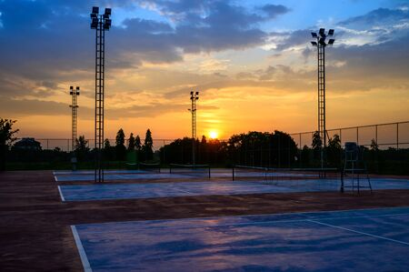 Landscape of tennis court on sunset time Фото со стока