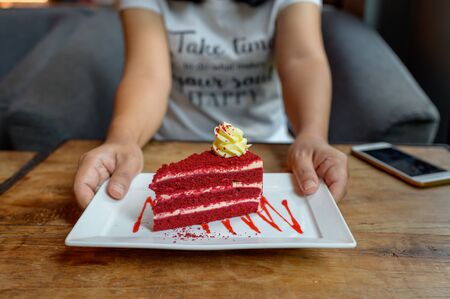 Red velvet cheese cake on white dish in woman hands serving on wood table Banque d'images - 132111039
