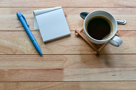 Coffee cup, blank notebook and pen on wood table