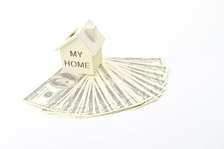 Home model on dollar banknotes pile isolate on white background, property ladder, mortgage and real estate investment concept Фото со стока