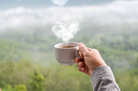 Hot coffee cup with heart shape steam in hand of woman, blurred landscape of forest in background Фото со стока