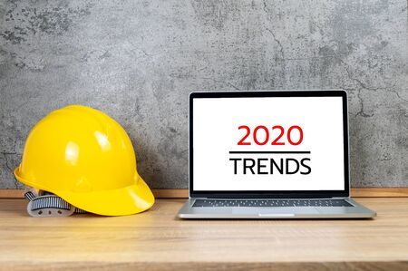 Yellow safety helmet and laptop computer with 2020 TRENDS text on white screen