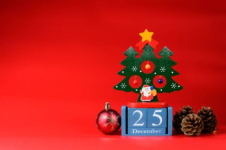 Christmas ornaments with 25 December wood calendar on red background