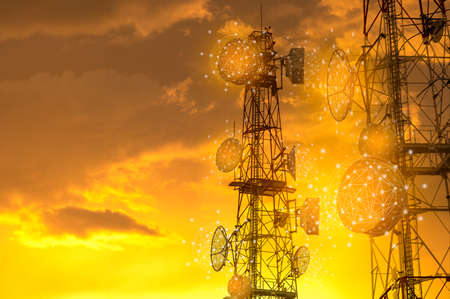 Telecommunication towers with wireless antennas on golden sunset sky